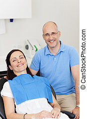 Dentist And Patient Smiling In Clinic - Portrait of dentist...