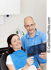 Patient Smiling While Looking At Xray In Clinic