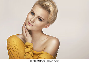 Delicate blonde woman wearing yellow sweater - Delicate...