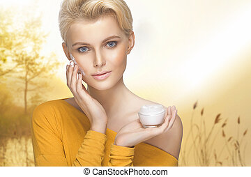 Portrait of young lady applying moisturizer cream on her pretty face