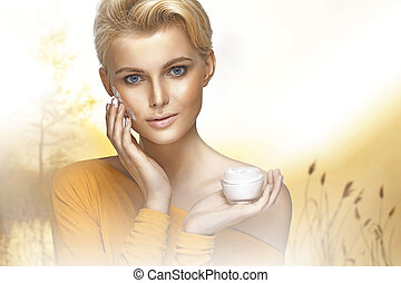 Portrait of young lady applying moisturizer cream on her clear face