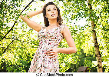 Young woman enjoying the fresh air in green forest.