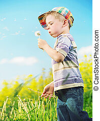 Young cheerful boy playing blow-ball - Cheerful litle kid...
