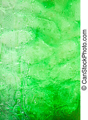 Green fizzy drink with ice cubes background