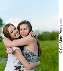 Two Teen Girl Friends Laughing in spring or summer outdoors...