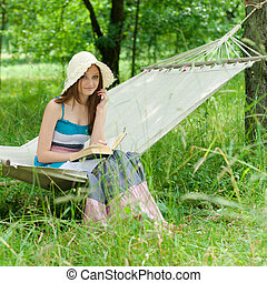 Happy young woman reading hammock - Happy young woman...