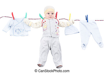 Little baby boy hanging on a clothesline, drying on...