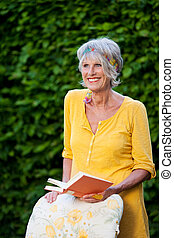relaxes senior lady with book in the garden
