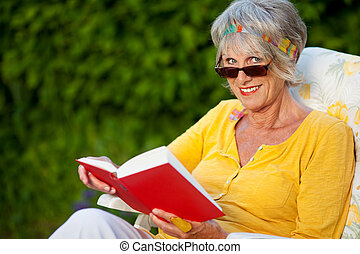 senior woman looking over sunglasses while reading a book