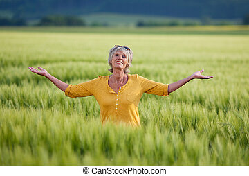 Senior Woman Enjoying Nature On Grassy Field - Happy senior...