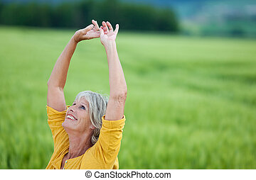 Senior Woman With Arms Raised Looking Up On Grassy Field -...