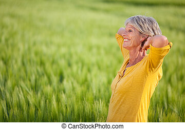 Senior Woman With Hands Behind Head On Grassy Field - Side...