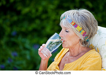 Senior Woman Drinking Sparkling Water In Park - Senior woman...