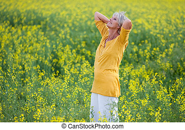 Senior Woman With Hand Behind Head Standing On Field - Happy...