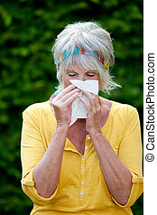 Senior Woman Blowing Nose In Tissue Paper - Senior woman...