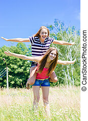 Two teenage girl friends having fun outdoors on summer day -...