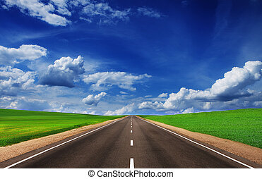 Asphalt road in green fields under beautiful sky. Way
