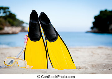 yellow fins and snorkelling mask on beach in summer holiday