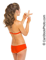 Young woman in swimsuit holding starfish . rear view