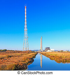 Power plant with smoke stacks, transmission tower and...