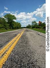 Rural Road - Empty road with curve ahead sign