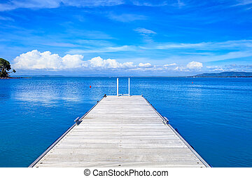 Wooden pier or jetty on a blue ocean. Beach in Argentario,...