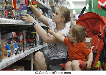 Mother and son shopping for toys - Mother and her two year...