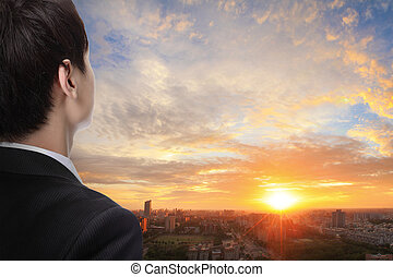 business man look sunrise in the city, concept for business