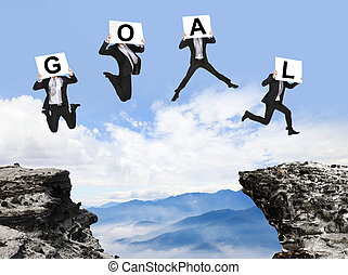 businessman jumping with GOAL text on danger precipice -...
