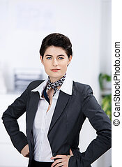 Confident Businesswoman With Hands On Waist In Office