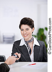 Receptionist Giving Cardkey To Customer At Reception - Happy...