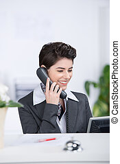 Receptionist Conversing On Landline Phone At Counter