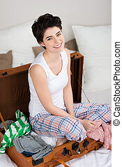 Young Woman Sitting In Suitcase On Bed