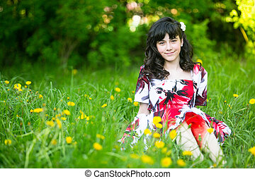 A teengirl sitting in the grass.