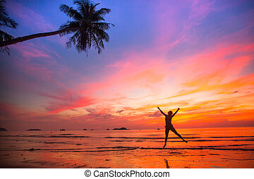 Young girl in a jump on the sea beach at sunset (concept of...