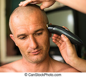 Close-up: Hairdresser shaving man with hair trimmer.