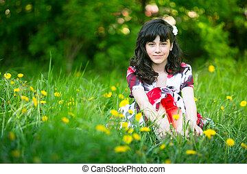 Beautiful teengirl sitting in the grass