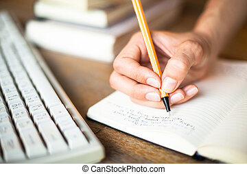 Woman hands writes a pen in a notebook, computer keyboard in...