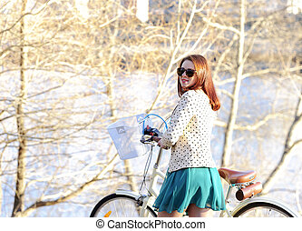 Girl walking with a bike in the park