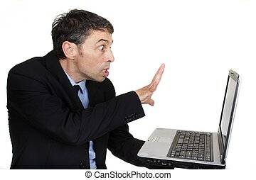 Businessman casting a spell on his laptop holding it in one...
