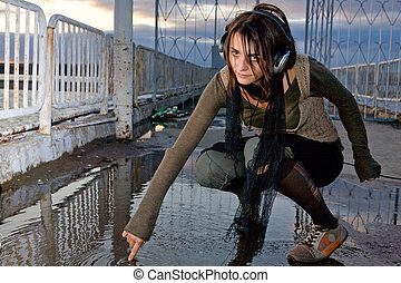Music art - Pretty girl in big professional headphones is...