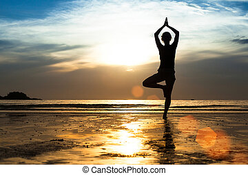 Silhouette of a young woman practicing yoga on the beach at sunset.