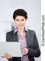 Young Businesswoman Holding Laptop In Office - Portrait of...