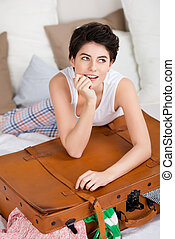 Smiling woman with a packed suitcase lying on her bed in her...