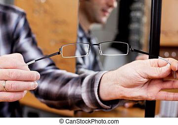 Optician's Hands Showing Flexibility Of Glasses - Cropped...