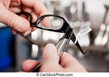 Opticians Repairing Glasses With Pliers - Closeup of...