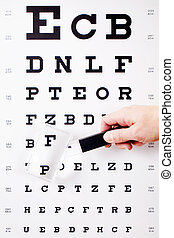 Hand Holding Magnifying Glass Against Snellen Chart -...