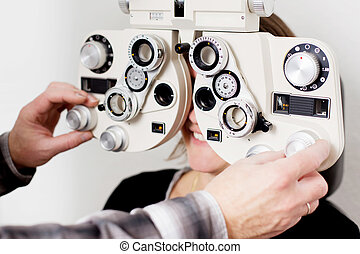 eye measurement at eye clinic - doctor examining patient at...