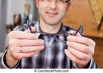 Optician Displaying Glasses In Store - Midsection of...