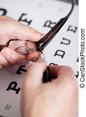Opticians Hands Repairing Glasses - Closeup of opticians...